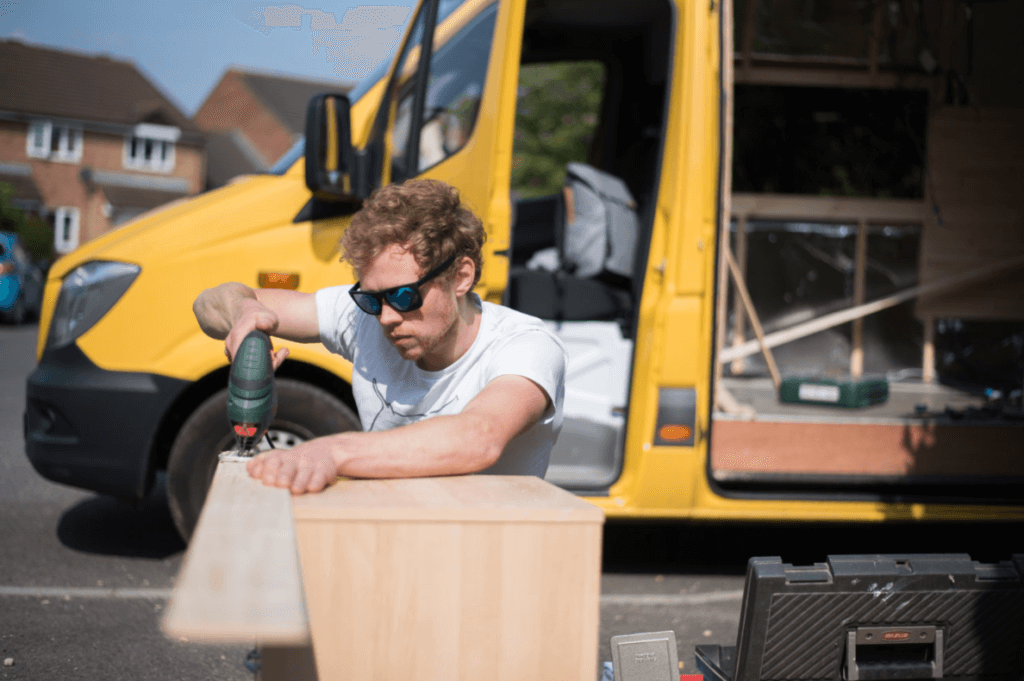 man cutting a piece of cladding with a jigsaw as part of a campervan conversion