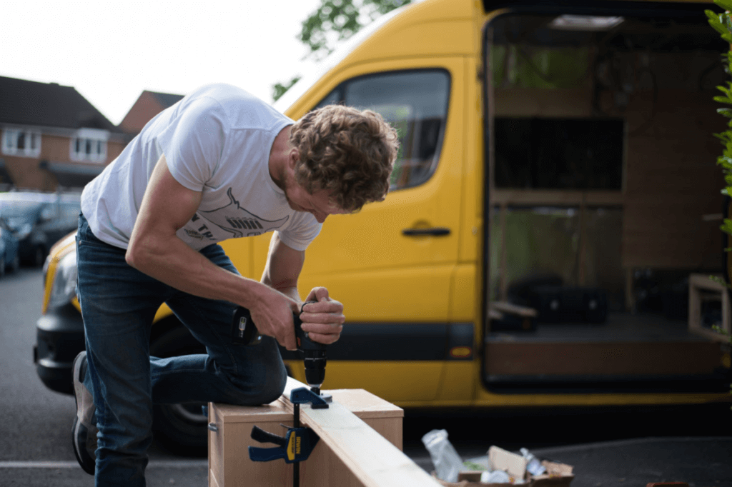 man using a hole saw to drill a piece of cladding in a campervan conversion
