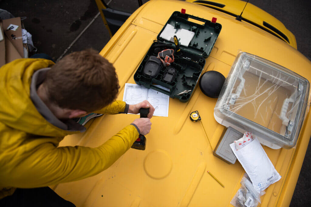 man drilling a hole in a yellow Sprinter van conversion campervan to install a skylight