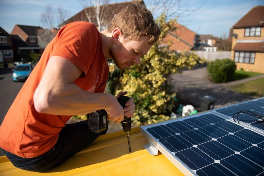 man drilling a hole in a van to install solar panels to a van conversion