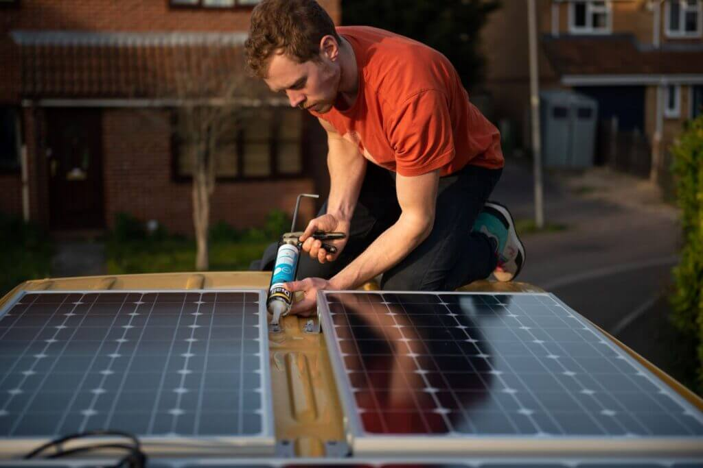 man using silicone to seal Renogy solar panels to the roof of a van conversion